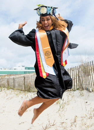 Student jumping in the air on the Atlantic City Campus Beach